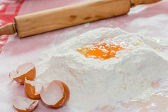 Making homemade pasta with flour and eggs on the kitchen counter Stock Photos