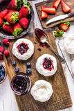 Making homemade pavlova dessert with berry fruits Royalty Free Stock Photo