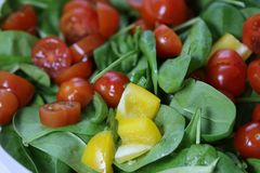 Making Homemade Salad with Spinach, Tomatoes and Yellow Pepper stock photo