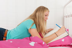 Making homework laying at bed Royalty Free Stock Photography