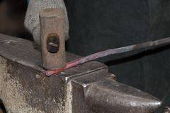 Making the horseshoe from heated red rod Stock Photo