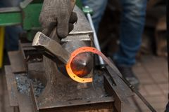 Making the horseshoe from heated red rod Royalty Free Stock Image