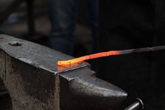 Making the horseshoe from heated red rod Stock Photos