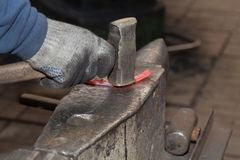 Making the horseshoe from heated red rod Stock Image
