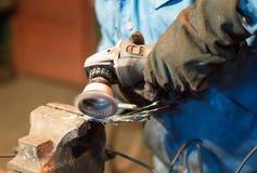 Making of horseshoe. Male worker polishing horseshoe Royalty Free Stock Image