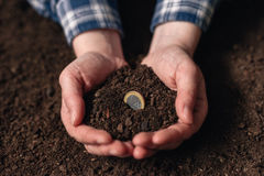 Making income from agricultural activity and earning extra money. Female farmer handful of soil with euro coin stock images