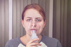 Making inhalation with nebulizer mask. Young woman is breathing with help of nebulizer mask, because she has chronic obstructive pulmonary disease stock photos