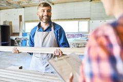 Making Inventory at Warehouse. Cheerful middle-aged craftsman and his unrecognizable colleague making inventory at spacious warehouse Stock Photo