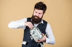 Making an investment. Businessman taking cash money out of glass jar for investing activities. Bearded man investing stock photo