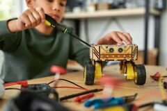 Free Making It Better. Close Up Of A Boy Using Screwdriver While Fixing Bolts On A Robot Vehicle. Smart Kids And STEM Stock Images - 176906104