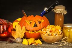 Making Jack o lantern. Carving the pumpkin. Hollowing out a scary pumpkin to prepare halloween lantern. Stock Photos