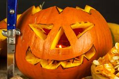 Making Jack o lantern. Carving the pumpkin. Hollowing out a scary pumpkin to prepare halloween lantern. Stock Image