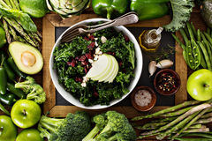 Making kale salad. Healthy eating concept with kale salad and green vegetables royalty free stock images