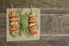 Making kebabs from chicken - raw meat on skewers on paper stock photo