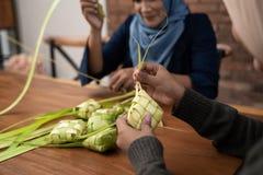 Making ketupat traditional indonesian food together. For eid mubarak celebration royalty free stock photo