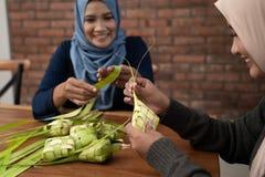 Making ketupat traditional indonesian food together. For eid mubarak celebration stock images