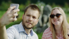 Making kissing selfie. Young couple of man and woman kissing and making selfie using smartphone sitting outside stock footage