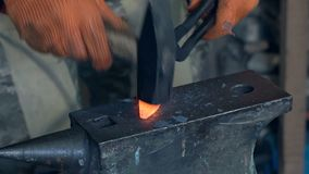 Forge hot metal. Making the knife out of metal at the forge. Close up blacksmith`s hands hitting hot metal with a massive hammer on an anvil stock video footage