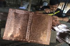Making koran (Quran) from brass Stock Images