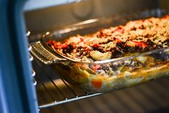 Making lasagna. Woman cooks lasagna in the kitchen Royalty Free Stock Image
