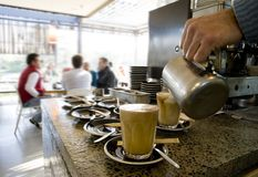 Making latte's and coffee. At a cafe with people in the background Royalty Free Stock Photography