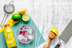 Making lemonade. Cookware, fruits, bottle of lemonade and ice cubes on wooden table background top view copyspace Stock Photo