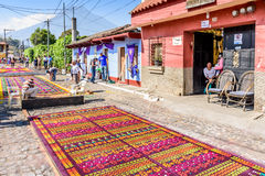 Making Lent carpets, Antigua, Guatemala. Antigua, Guatemala - March 26, 2017: Locals make dyed sawdust procession carpets during Lent against backdrop of Agua stock image