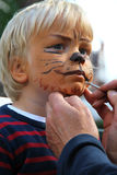 The making of a lion. The face of a young child being made to look like a ferocious lion by a make-up artitst stock photos