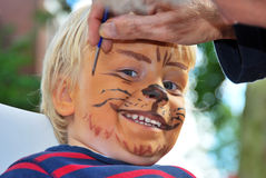 The making of a lion. The face of a young child being made to look like a ferocious lion by a make-up artist Royalty Free Stock Images