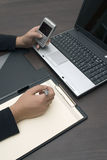 Making a List. Business man writing a list of contacts from a cellphone & laptop Royalty Free Stock Images