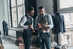 Making a list of requirements. Two young fashionable men having a discussion while standing in workshop royalty free stock image