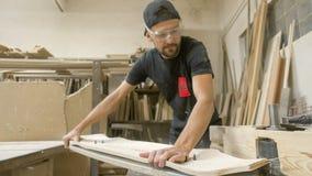 Making of Longboard Deck. Young artisan man cutting longboard deck Stock Photos