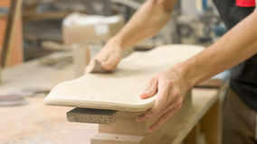 Making of Longboard Deck. Young artisan man sandering top layer of longboard Royalty Free Stock Photos