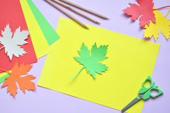 Making maple leaf from colored paper with your own hands for decoration of greeting card. Handmade crafts. Hello Autumn concept. C. Hildren's DIY. Copy royalty free stock images