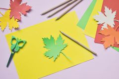 Making maple leaf from colored paper with your own hands for decoration of greeting card. Handmade crafts. Hello Autumn concept. C. Hildren's DIY. Copy royalty free stock photo