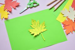 Making maple leaf from colored paper with your own hands for decoration of greeting card. Handmade crafts. Hello Autumn concept. C. Hildren's DIY. Copy stock image