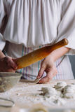 Making meat dumpling with wooden rolling pin. Royalty Free Stock Image