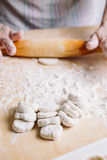Making meat dumpling with wooden rolling pin. Royalty Free Stock Photo