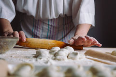 Making meat dumpling with wooden rolling pin. Royalty Free Stock Photography