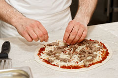 Making of a meat pizza. In a restaurant royalty free stock photo