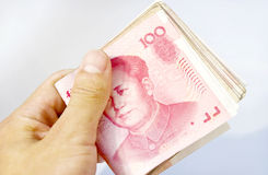 Making money. Man is holding a pile of Chinese money 100 yuan Royalty Free Stock Images