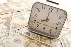 Making Money. Money Making Time With Clock On American Tender Royalty Free Stock Photography