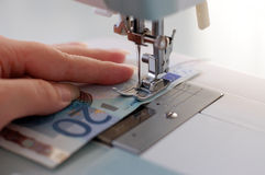 Making Money. Sewing money with the sewing machine Stock Photos