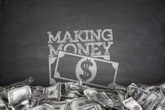Making money on blackboard Royalty Free Stock Image