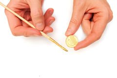 Making money. Gold coin and a brush in male hands. Making money. Gold coin and a brush with paint in male hands isolated on white background royalty free stock photo