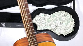 Acoustic guitar neck up close and out of focus, full guitar case with money in focus, sharp depth of field