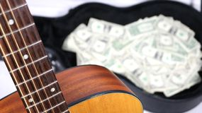 Acoustic guitar corner and neck up close in focus, money in case out of focus, strong depth of field stock image