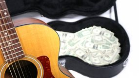 Partial acoustic guitar in focus, case with money out of focus, sharp depth of field