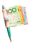 Making money with a pen. A roll of colourful Australian banknotes held by a pen like the shape of a flag Royalty Free Stock Photography