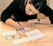 Making money in a time of crisis concept. Financial crisis solution concept .Making money concept . a woman drawing dollars on a black table . forging fake money Stock Images
